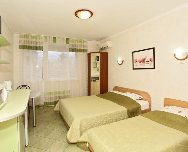 номер в отеле с зелеными кроватями