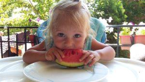 двовольная девочка кушает арбуз в Коктебеле